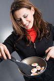Woman cooking eggs Stock Photography