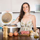 Woman cooking with electric multicooker Stock Photo