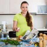 Woman cooking fish at home Royalty Free Stock Image
