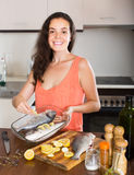 Woman cooking fish at home kitchen Stock Image