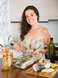 Woman cooking fish at home kitchen Royalty Free Stock Images