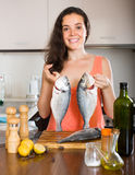 Woman cooking fish at kitchen Royalty Free Stock Images