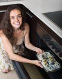 Woman cooking fish at kitchen Royalty Free Stock Image