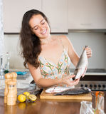 Woman cooking fish at kitchen Stock Images