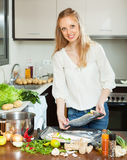 Woman cooking fish in sheet pan Stock Images