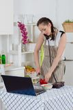 Woman cooking food in the kitchen. Stock Images