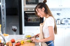 Woman cooking food in kitchen room concept, Young asian female making salad. With vegetables for dinner healthy food with cocktail, wine drinking Stock Photos