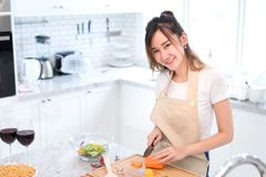 Woman cooking food in kitchen room concept, Young asian female making salad. With vegetables for dinner healthy food with cocktail, wine drinking Royalty Free Stock Photography