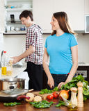 Woman cooking food while man washing dishes Royalty Free Stock Photo