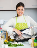 Woman cooking fresh rainbow trout. Cheerful woman arranging fresh rainbow trout on baking sheet Royalty Free Stock Photo
