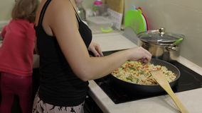 Woman cooking fry meal. Fig with asparagus, pepper, corn and carrot. Woman cooking fry meal in the kitchen with her daughter on background. Fig with asparagus stock footage