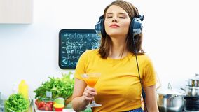 Woman cooking with fun. Girl drinking juice in kitchen. And listen music Stock Photos