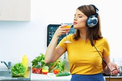 Woman cooking with fun. Girl drinking juice in kitchen. And listen music Stock Image