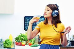 Woman cooking with fun. Girl drinking juice in kitchen. And listen music Royalty Free Stock Photo