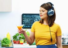Woman cooking with fun. Girl drinking juice in kitchen. And listen music Royalty Free Stock Photos