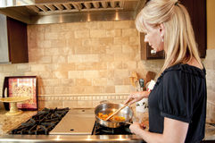 Woman cooking on a gas range Stock Photo
