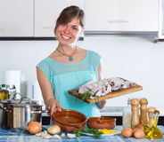 Woman cooking hake in ceramic pot Royalty Free Stock Photography