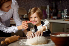 Woman cooking and having fun with little girl. Young women in formal clothing having fun while making dough with little adorable girl in modern kitchen Royalty Free Stock Photo