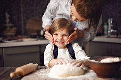 Woman cooking and having fun with little girl. Young women in formal clothing having fun while making dough with little adorable girl in modern kitchen Stock Photo