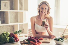 Woman cooking healthy food. Beautiful young sportswoman is looking at camera and smiling while cooking healthy food in kitchen at home Royalty Free Stock Photo