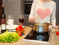 Woman cooking at home preparing pasta in a kitchen royalty free stock images