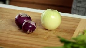 Woman cooking at home - preparing to cut onions. Woman cooking at home - preparing to cut red and white onions on wooden cutting board stock video footage