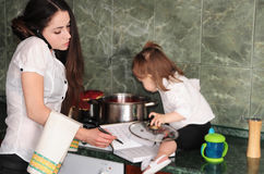 Woman cooking at home. Woman tries to work at home with a baby Stock Photography