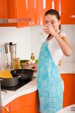 Woman cooking in the kitchen ant drinking wine Royalty Free Stock Photos