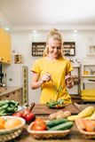 Woman cooking on the kitchen, eco food preparation. Smiling woman cooking on the kitchen, healthy eco food preparation. Vegetarian diet, fresh vegetables and Stock Photo