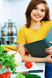 Woman cooking in kitchen with menu book. Royalty Free Stock Images