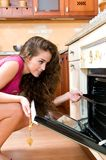 Woman cooking in the kitchen opening the oven door Stock Images