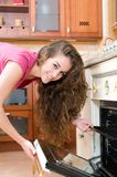 Woman cooking in the kitchen opening the oven door Royalty Free Stock Photography