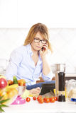 Woman cooking in the kitchen. Portrait of a smiling attractive woman making call while cooking in the kitchen Stock Photo