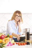 Woman cooking in the kitchen. Portrait of a smiling attractive woman making call while cooking in the kitchen Stock Photography