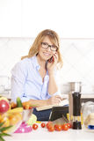 Woman cooking in the kitchen. Portrait of a smiling attractive woman making call while cooking in the kitchen Stock Image