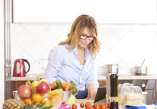 Woman cooking in the kitchen. Portrait of a smiling attractive woman writing to her recipe book while cooking in the kitchen Royalty Free Stock Photography
