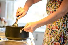 Woman cooking. In the kitchen, sharing meat spreads Stock Photo