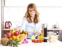 Woman cooking in the kitchen. Shot of a woman peeling vegetables while cooking in hter kitchen Stock Photos