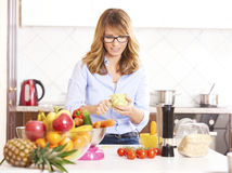 Woman cooking in the kitchen. Shot of a woman peeling vegetables while cooking in hter kitchen Stock Images
