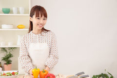 Woman cooking in kitchen with space for copy. Royalty Free Stock Image