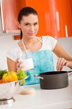 Woman cooking in the kitchen, tasting soup Royalty Free Stock Photography
