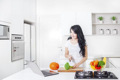 Woman cooking with laptop in kitchen Stock Photography