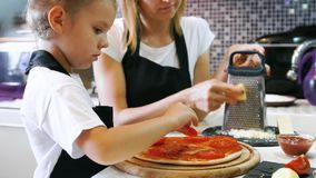 Woman cooking with little girl. Young woman with her little adorable daughter in formal clothing making pizza in modern kitchen at home stock footage