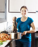 Woman cooking with lobster in home Stock Photo