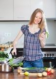 Woman cooking lubina fish in fryingpan Stock Image