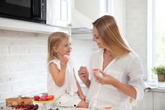 Woman cooking macarons at the kitchen with her little daughter Royalty Free Stock Images