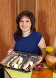 Woman cooking the mackerel with cranberries Stock Photos