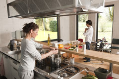 Woman cooking man with house model Stock Photography