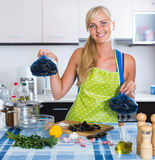 Woman cooking marinade for tasty mussels at kitchen table Royalty Free Stock Photography