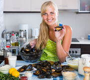 Woman cooking marinade for tasty mussels at kitchen table Stock Image